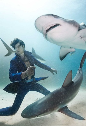 Caribbean reef sharks cirlcle whilst the model wears colour drenched coats on a sea of grey. On location in the Bahamas. Styled by Damian Foxe and Millecent Simon for The Financial Times, UK